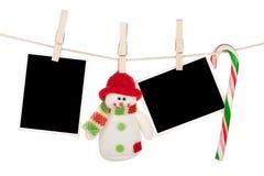 Het lege fotokaders en sneeuwman hangen op de drooglijn Stock Foto's