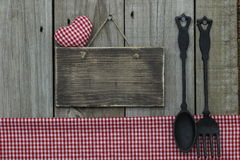 Het lege houten teken met rood ginganghart en tafelkleed en het gietijzer lepelen en vork Royalty-vrije Stock Afbeeldingen