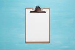 Het lege klembord op achtergrond van de pastelkleur de blauwe kleur met vlakke exemplaar ruimte, minimale stijl, legt Stock Afbeelding
