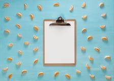 Het lege klembord op lijst van de pastelkleur de blauwe kleur met de plakken van de citrusvruchtenmandarijn, minimale vlakke stij Stock Foto's
