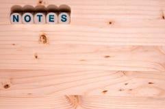 Het lege lichte hout vult dit die malplaatjebeeld met de woordnota's in blokken langs de bovenkant nauwkeurig worden beschreven stock foto