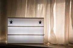 Het lege lichte vakje op venstervensterbank, met gordijnen en warme licht voegen eigen bericht toe royalty-vrije stock afbeeldingen