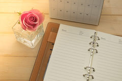 Het lege notitieboekje, kalender en roze nam in glasvaas toe op houten achtergrond Royalty-vrije Stock Foto