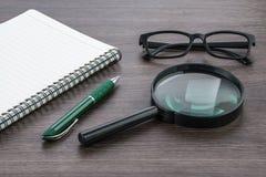 Het lege notitieboekje met Magnifier op deskr, sluit omhoog Royalty-vrije Stock Fotografie