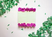 Het lege notitieboekje verfraaide purpere bloemen op een witte achtergrond, hoogste mening Blocnote met groen bladeren en viooltj royalty-vrije stock afbeelding