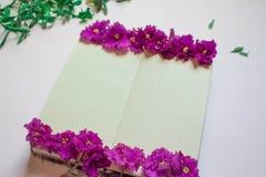 Het lege notitieboekje verfraaide purpere bloemen op een witte achtergrond, hoogste mening Blocnote met groen bladeren en viooltj royalty-vrije stock foto's