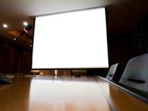 het lege projecter witte scherm op plicht in de donkere ruimte Royalty-vrije Stock Afbeelding