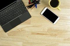 Het lege scherm smartphones en labtop op de houten Desktop en a stock foto