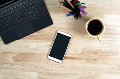 Het lege scherm smartphones en labtop op de houten Desktop en a royalty-vrije stock fotografie