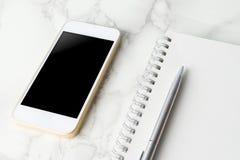 Het lege slimme telefoonscherm met leeg notitieboekje op marmer royalty-vrije stock afbeeldingen