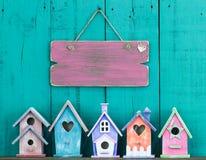 Het lege teken hangen op omheining door rij van vogelhuizen stock foto