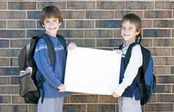 Het Lege Teken van de Holding van de Jonge geitjes van de school Royalty-vrije Stock Afbeeldingen