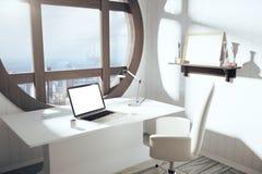 Het lege witte laptop scherm op witte lijst met stoel en ronde wi royalty-vrije stock foto