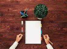 Het lege witte notitieboekje van de vrouw de handen en Stock Foto