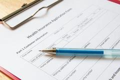 Het lege ziektekostenverzekeringaanvraagformulier met pen wacht op vulling royalty-vrije stock afbeeldingen