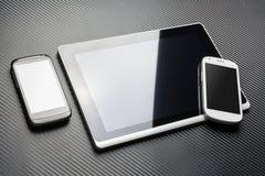 Het lege Zwarte Mobiele Liggen naast een Bedrijfstablet met Bezinning en Wit Smartphone op het is Hoek, allen boven een Koolstofl Stock Afbeelding