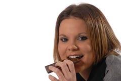 Het leggen op vloer die een chocoladereep eet Royalty-vrije Stock Fotografie