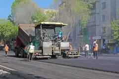 Het leggen van asfalt op de bestrating stock afbeeldingen