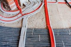 Het leggen van elektriciteitskabels, netwerken, het verwarmen Golflijnen op beton stock afbeeldingen