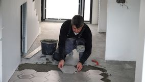Het leggen van hexagon tegels op vloer Het neerdrukken en het regelen stock videobeelden