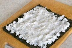 Het leggen van rijst op een noriblad wanneer het maken van sushi rolt Stock Foto