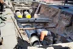 Het leggen van riool en gaspijpen onder de grond in een stadsstraat Stock Fotografie