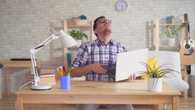 Het lekken van het plafond aan een ongerust gemaakte jonge mens met een laptop zitting bij een lijst stock video