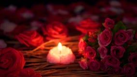 Het lengteonduidelijke beeld van bloembloemblaadjes, nam boeket en kaars het branden toe De dag van de valentijnskaart stock videobeelden