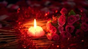 Het lengteonduidelijke beeld van bloembloemblaadjes, nam boeket en kaars het branden toe De dag van de valentijnskaart stock video