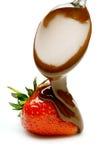Het lepelen van chocolade op een aardbei Stock Afbeeldingen