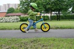 Het leren om op een eerste fiets te berijden Stock Foto's
