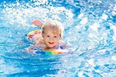 Het leren te zwemmen Jonge geitjes in zwembad stock afbeeldingen