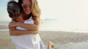 Het lesbische paar loopt aan elkaar en omhelst op een strand stock footage