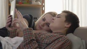 Het lesbische paar rust op de laag, gebruikend tabletcomputer, scrollend foto's op tablet, het glimlachen, familieidylle, liefde stock footage