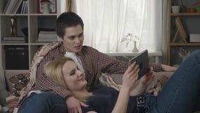 Het lesbische paar rust op de laag, gebruikend tabletcomputer, scrollend foto's op tablet, houdend handen, het glimlachen stock video