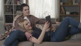 Het lesbische paar rust op de laag, gebruikend tabletcomputer, scrollend foto's op tablet, houdend handen, knuffelend 60 stock footage