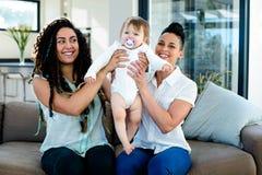 Het lesbische paar spelen met hun baby Stock Afbeeldingen
