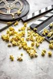 Het letten op film met dicht omhoog popcorn op grijze achtergrond stock foto