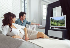 Het letten op TV die op bed liggen Stock Fotografie