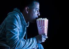 Het letten op TV, die popcorn eet Royalty-vrije Stock Afbeeldingen
