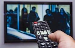Het letten op TV en het gebruiken van ver controlemechanisme Royalty-vrije Stock Afbeelding