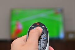 Het letten op TV en het gebruiken van ver controlemechanisme Stock Afbeeldingen