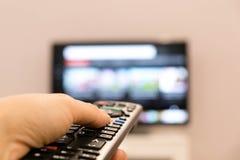 Het letten op TV en het gebruiken van ver controlemechanisme De afstandsbediening van de holdingsTV van de hand met een televisie Stock Afbeelding