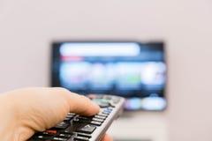 Het letten op TV en het gebruiken van ver controlemechanisme De afstandsbediening van de holdingsTV van de hand met een televisie Stock Fotografie