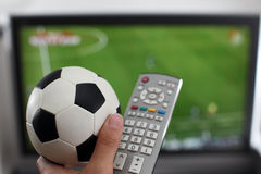 Het letten op TV met bal en ver Stock Foto's