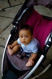 Het letten op van de baby binnen haar wandelwagen Stock Foto