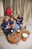 Het letten op van de familie sporten op TV. Stock Foto