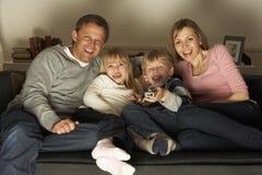 Het Letten op van de familie Televisie samen Stock Foto's