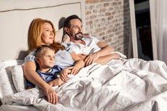 Het letten op van de familie televisie thuis stock fotografie