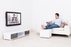 Het Letten op van de mens Televisie stock afbeelding
